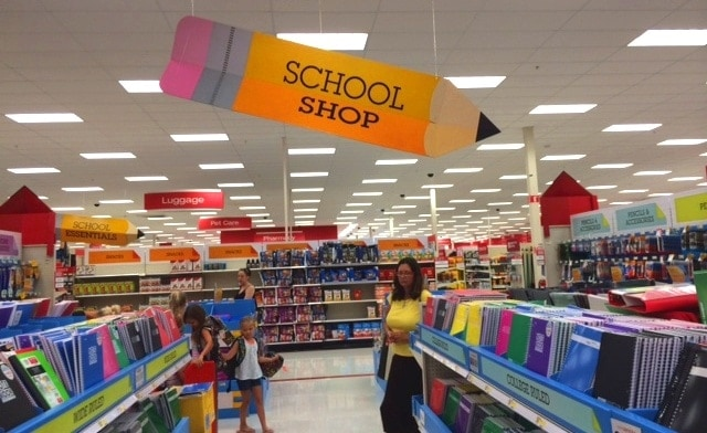 school supply aisle with large pencil sign hanging from ceiling