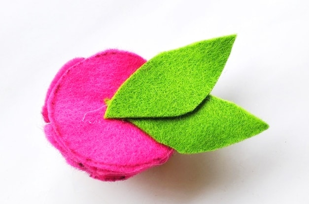 two green felt leaves attached to the bottom of a pink flower