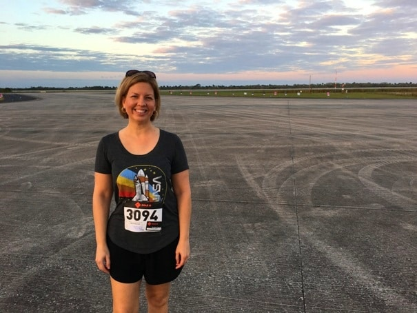 Woman standing on runway wearing race number