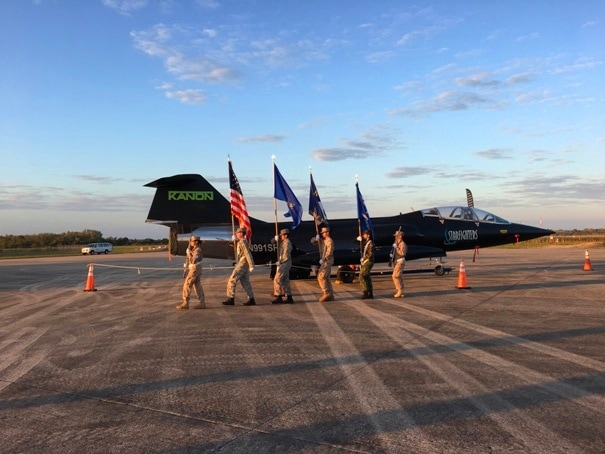 JROTC holding flags walking by a jet