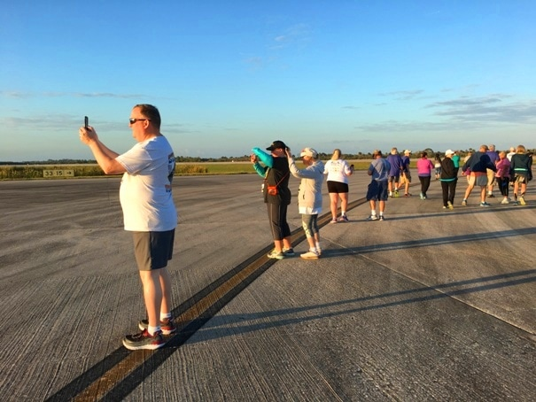 race runners stopping on a runway to take pictures in the morning light