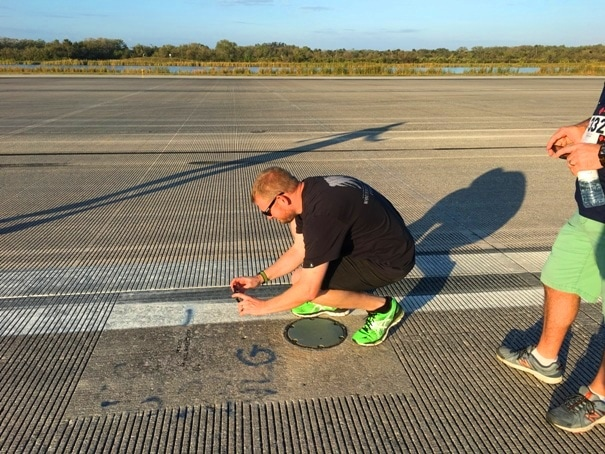 man kneeling on runway taking pictures with a phone