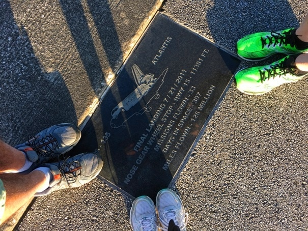 three pairs of sneakers standing on plaque with space shuttle image
