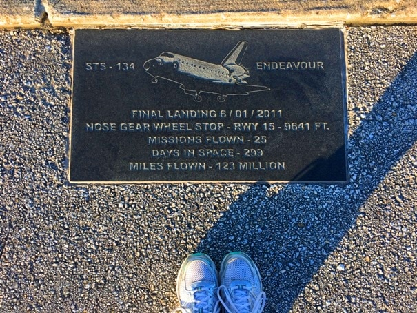 tennis shoes standing next to plaque with space shuttle