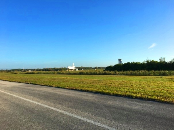 runway with grass and space shuttle and tower in the distance