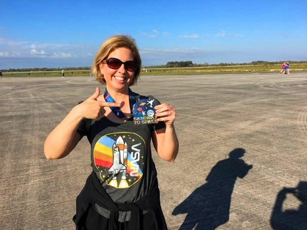 woman wearing a space shuttle t-shirt and a race medal