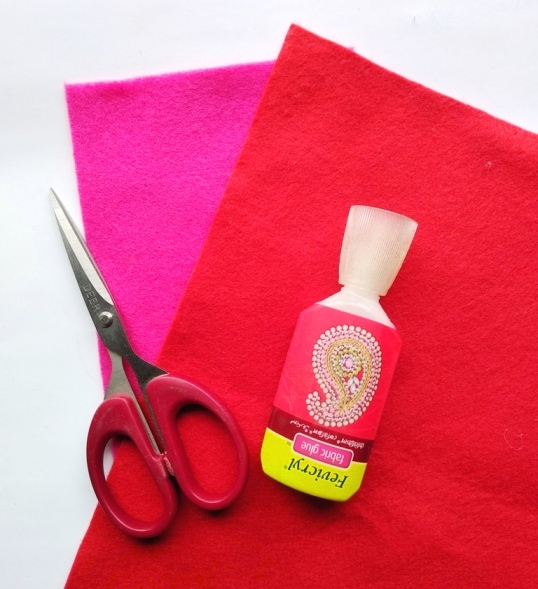 pink and red felt with scissors and glue
