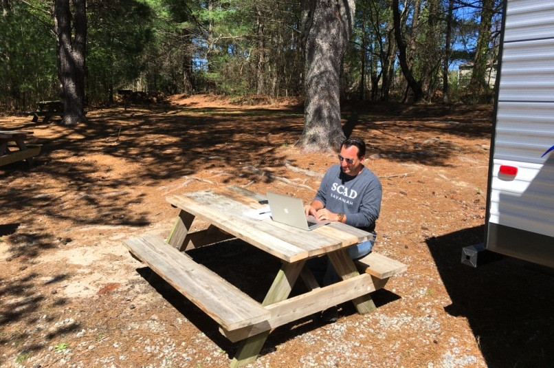 man sitting behind computer on wooden picnic table in the woods at RV park
