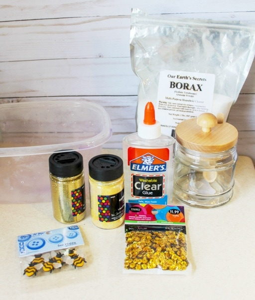 glitter glue bottle sequins bee buttons and bag of borax on a table for slime recipe