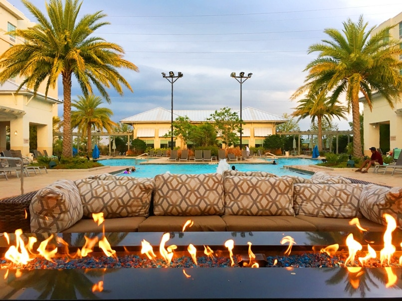 firepit with flames by pool surrounded by palm trees