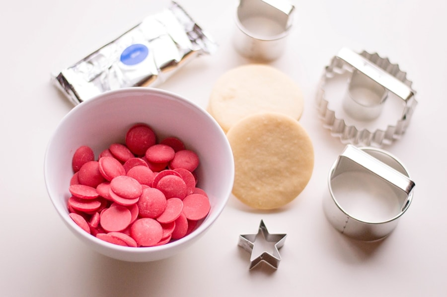 white bowl of red candy melts sugar cookie star cookie cutter circle cookie cutters on white table