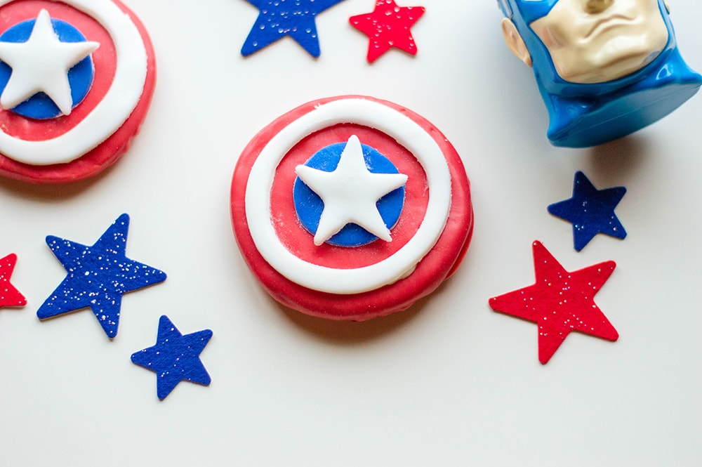 red cookie with white circle and blue dot in center topped with white star captain america head