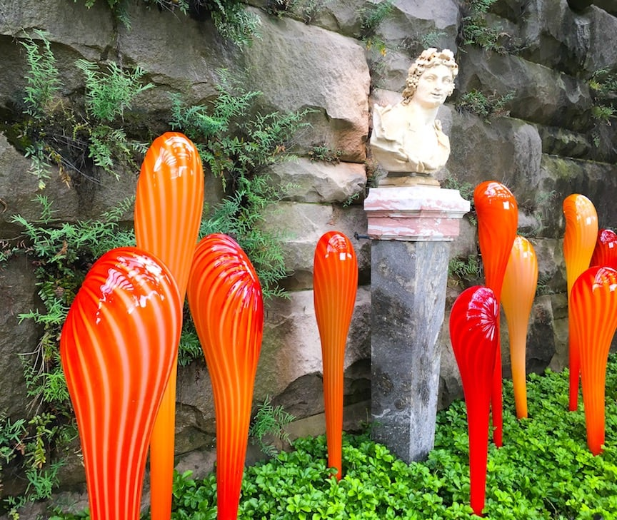 red and orange glass sculptures against stone wall with bust