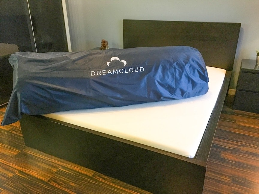 Dreamcloud Mattress Rolled Up In A Blue Duffel Bag Lying Onto Of Bed Frame