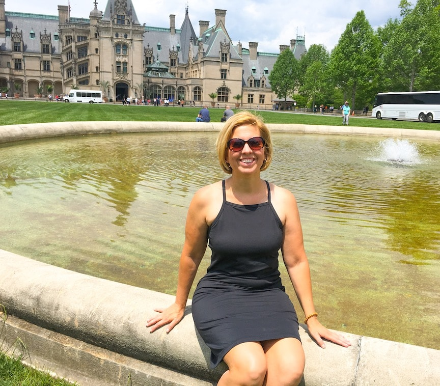 sitting on fountain in front of Biltmore Estate house