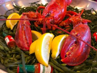 red lobster with fresh cut yellow lemons and tabasco sauce mini bottles