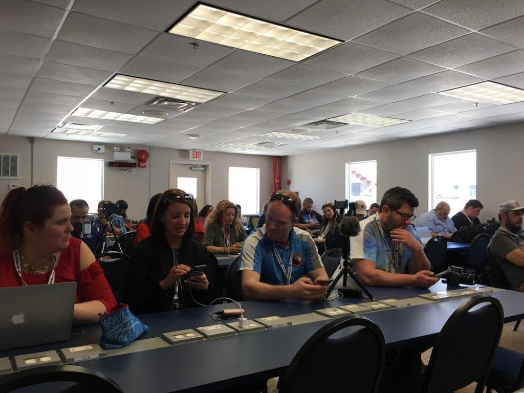 NASA Social participants sitting at long tables using cell phones