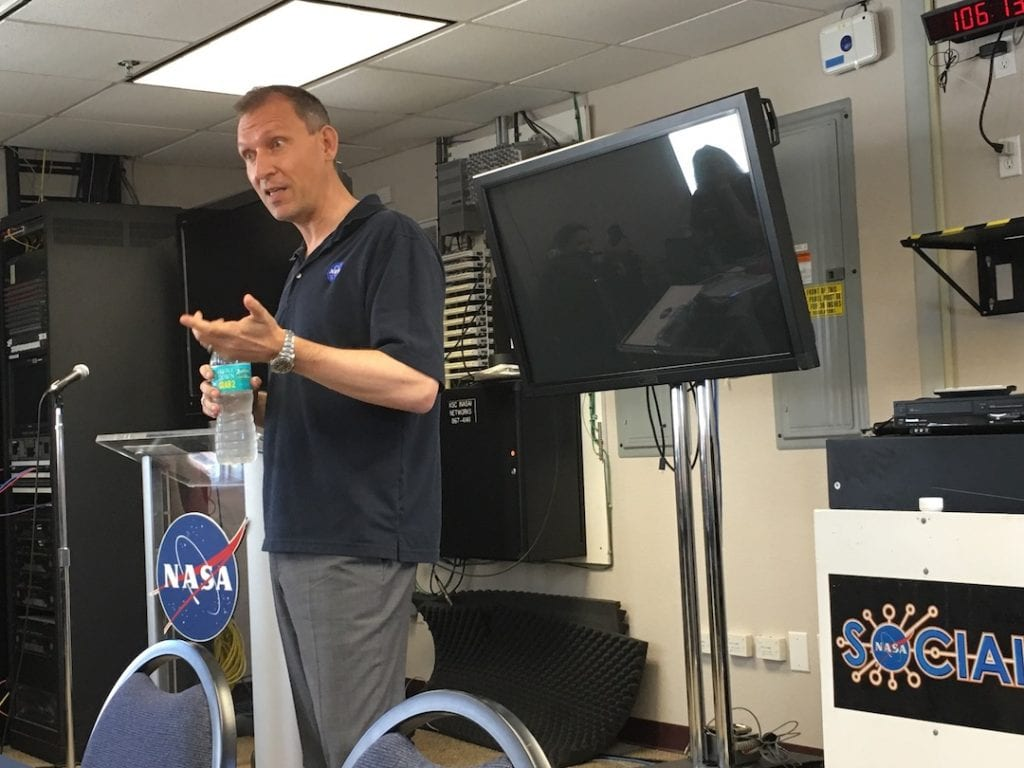 Scientist talking in front of a NASA logo and TV screen