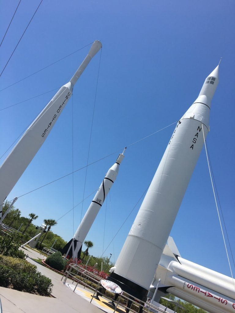Historic Rockets standing upright against a bright blue sky at Kennedy Space Center