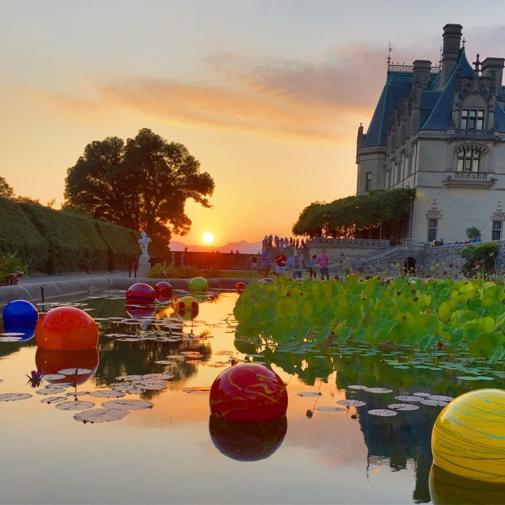 sunset behind the mountains Chihuly glass in pond at Biltmore Estate