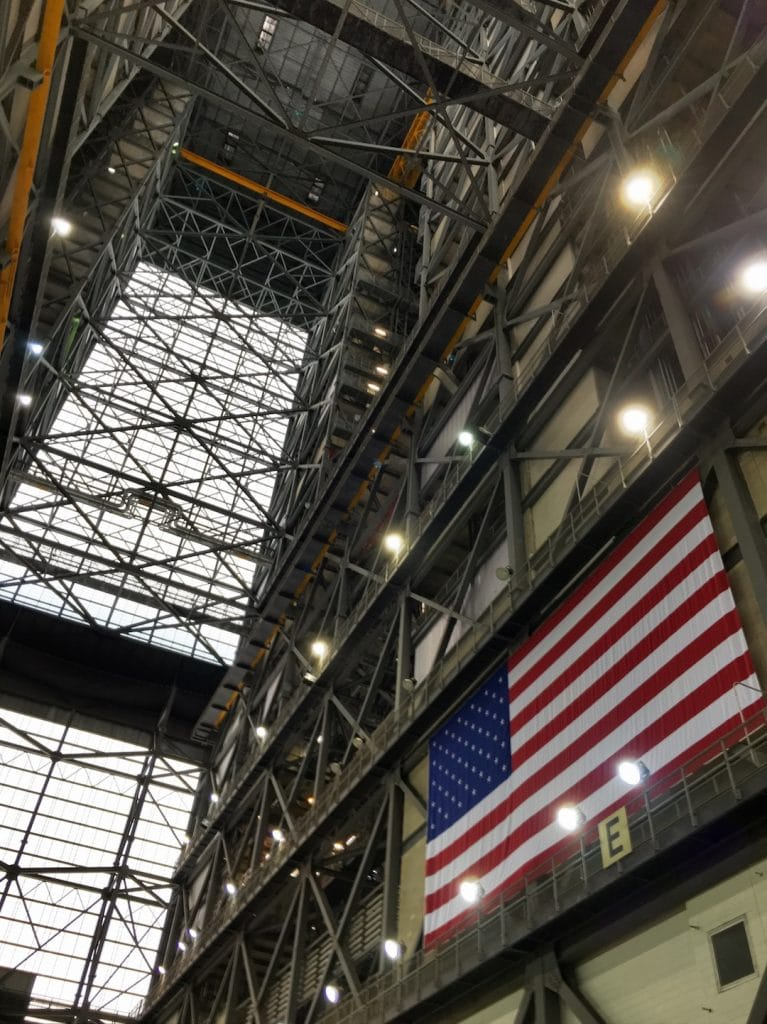 Soaring ceilings of the VAB at NASA with large American flag
