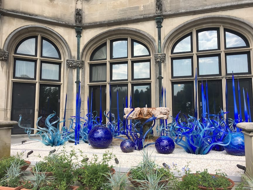 blue glass Chihuly sculptures in front of Biltmore House windows