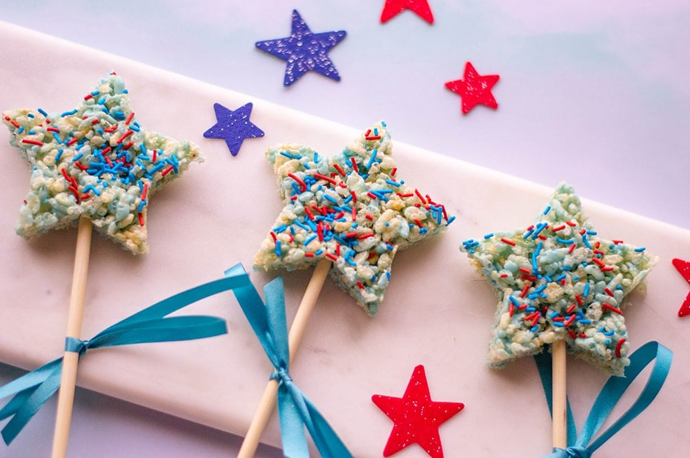 star shaped Rice Krispies treats with blue and red sprinkles on a pink background