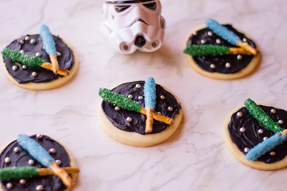 Star Wars light saber cookies with blue and green light sabers on black frosting