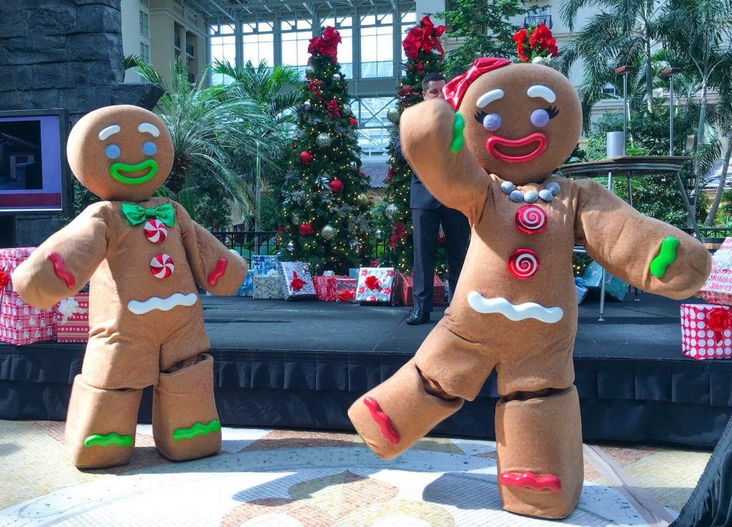gingerbread men costumes in front of Christmas trees