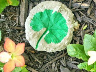 Green Leaf imprint in grey cement decorative garden stone against mulch