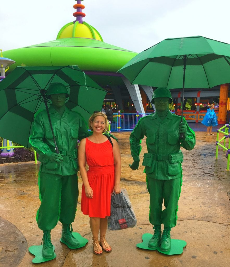 green army men characters with woman in red dress holding umbrellas in the rain at Toy Story Land at Disney's Hollywood Studios
