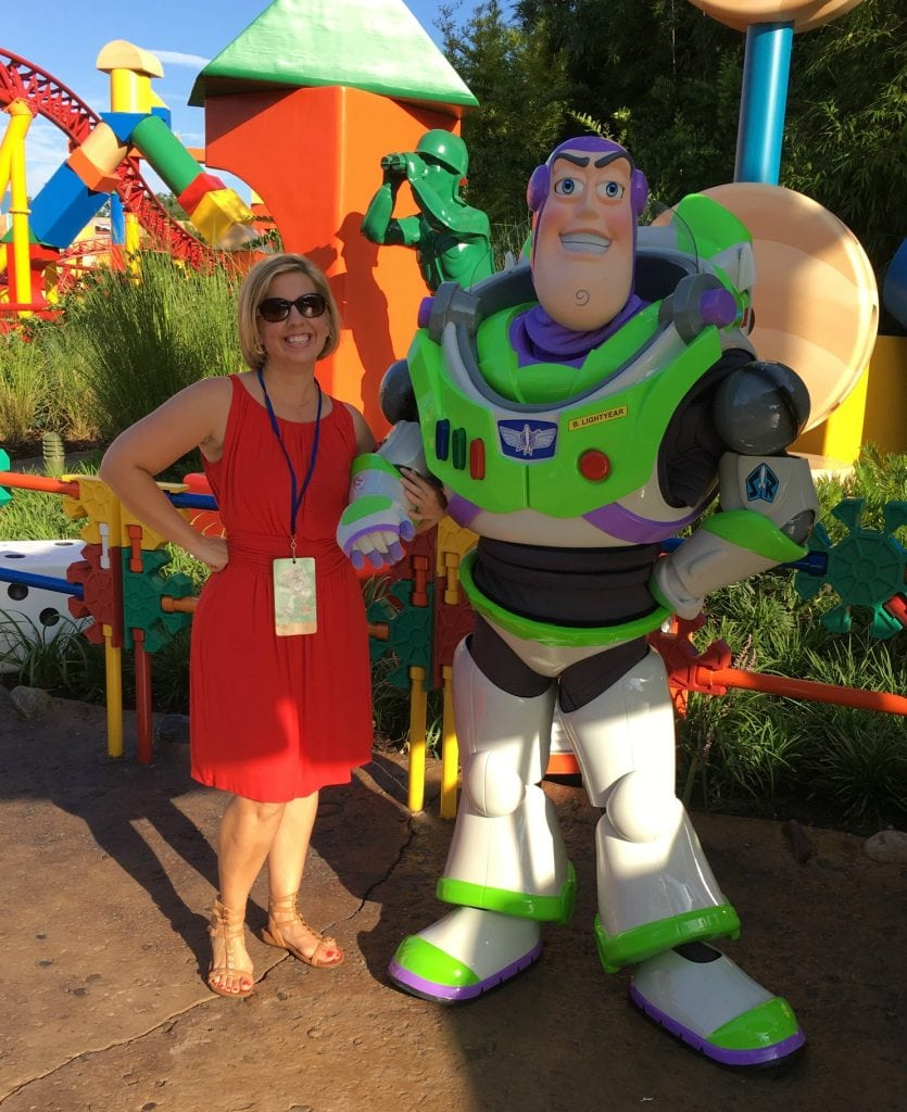 woman in red dress with buzz lightyear toy story land