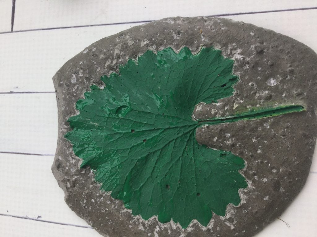green painted leaf in decorative cement garden stone