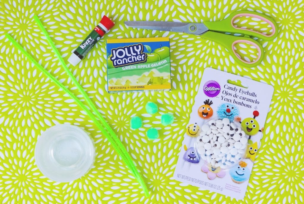 green pipe cleaners gelatin box scissors glue and candy eyes