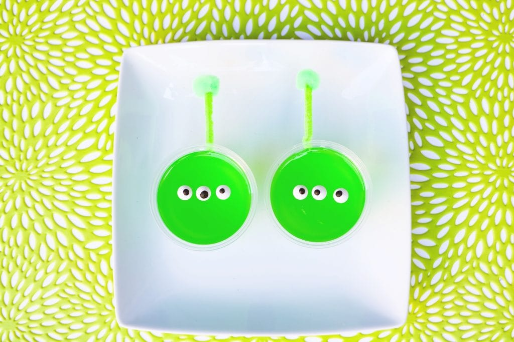green jello Toy Story alien snack cups with candy eyes and pipe cleaner antennas