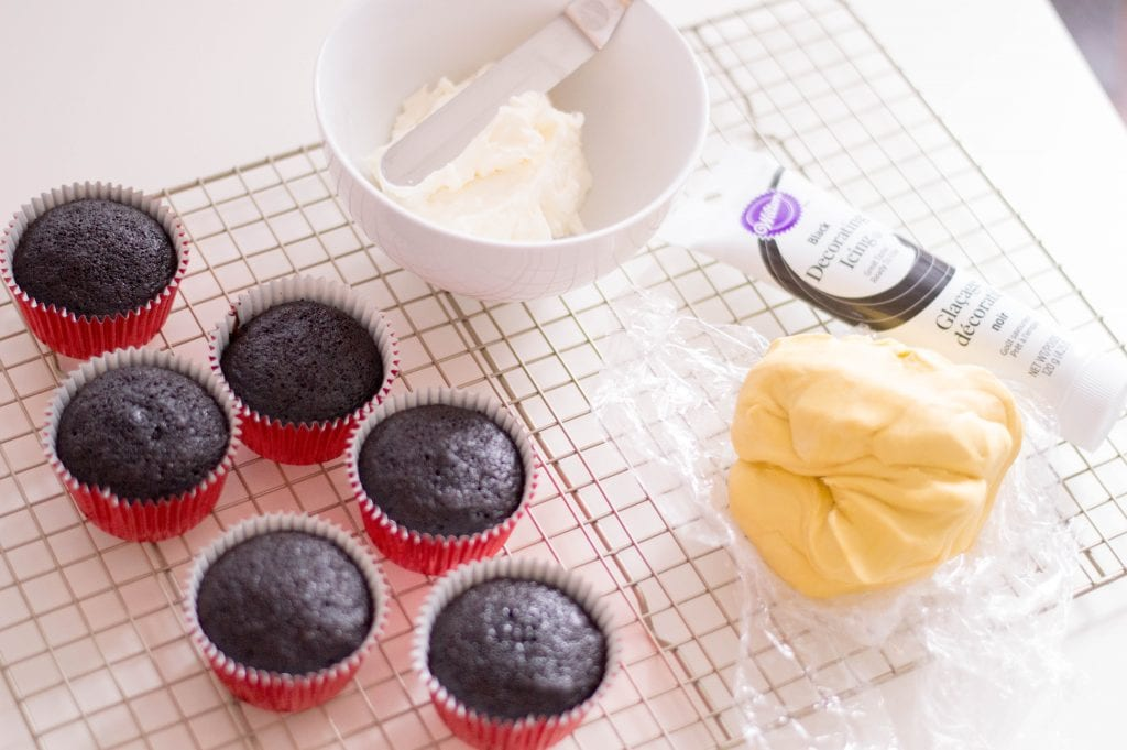 chocolate cupcakes in red wrappers with bowl of white frosting and yellow fondant