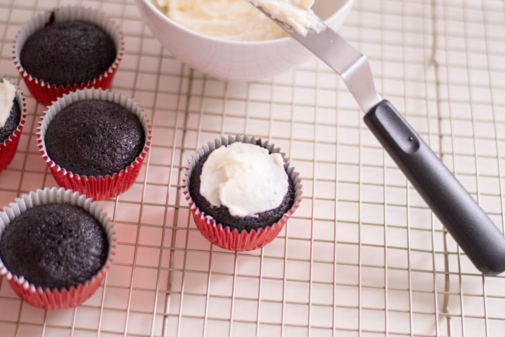 chocolate cupcake with red wrapper topped with white frosting on a baking rack