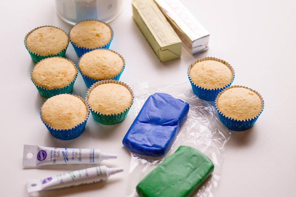 unfrosted cupcakes, blue and green fondant, black icing gel, butter ingredients for edible crayons