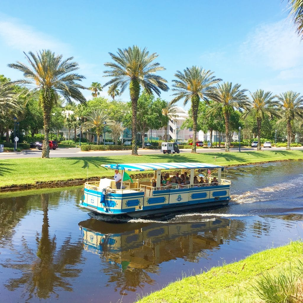 boat in canal with green grass on banks and palm trees at Disney World