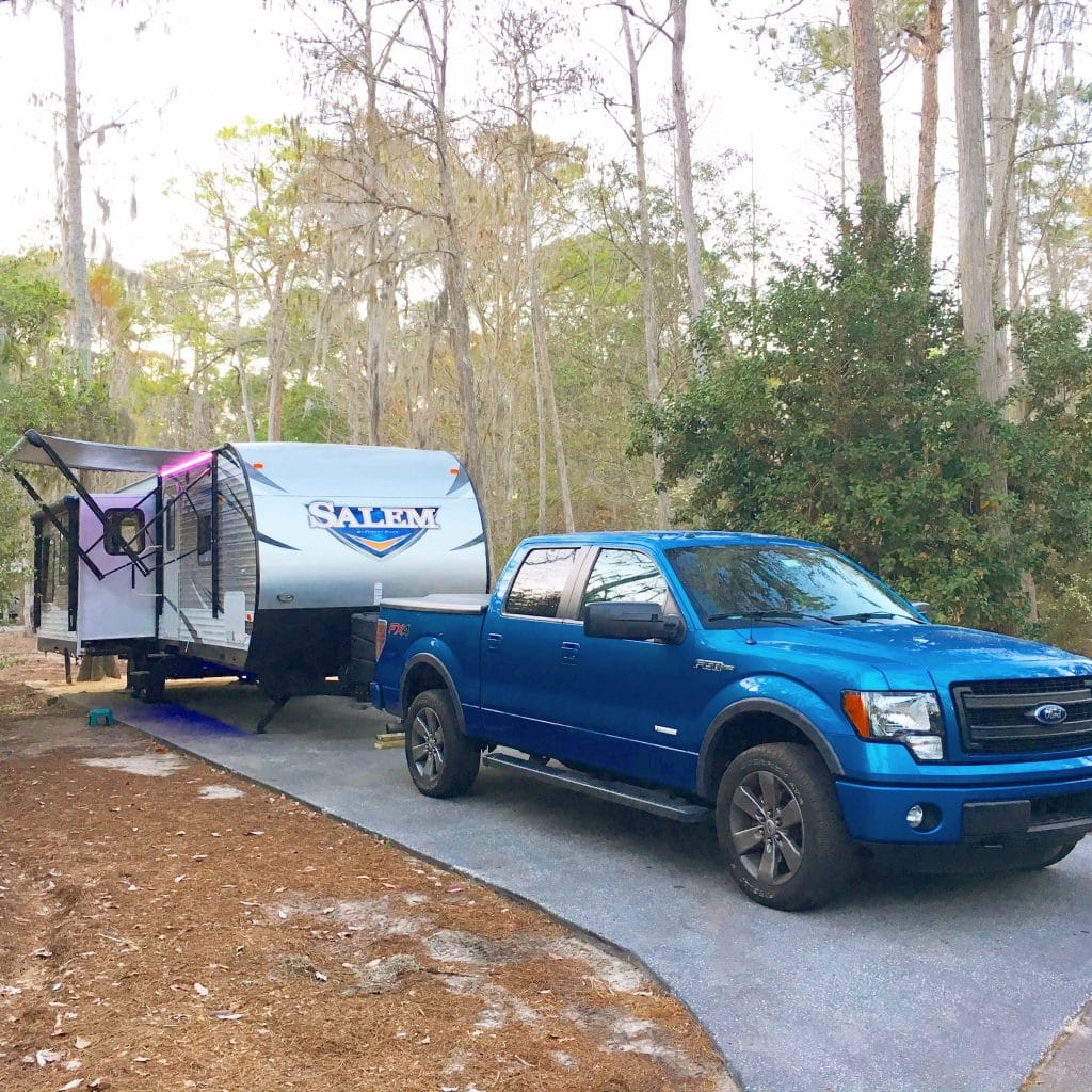 blue truck hooked up to travel trailer rv in campsite