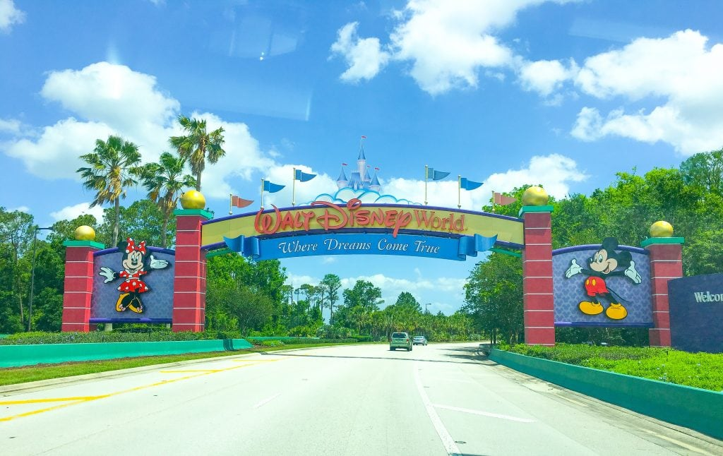 Walt Disney World Sign with palm trees, blue sky and white clouds in the background