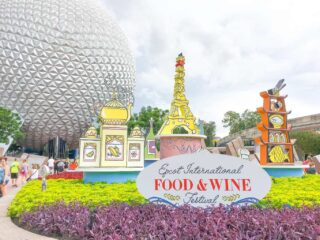 Eiffel Tower and tea pot signs in front of Epcot Spaceship Earth Ball