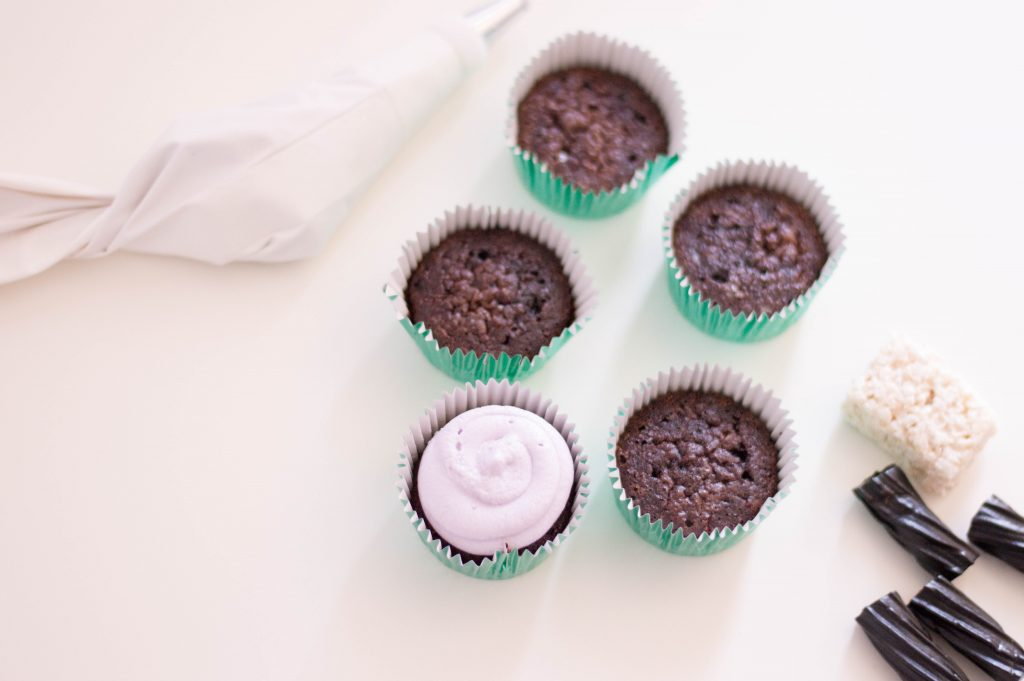 chocolate cupcakes with purple frosting on white background