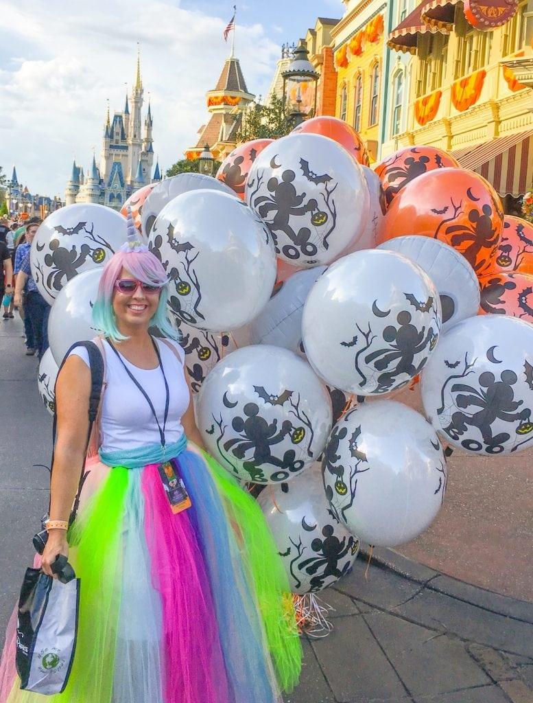 rainbow tulle skirt unicorn costume holding halloween balloons in front of castle at Disney world