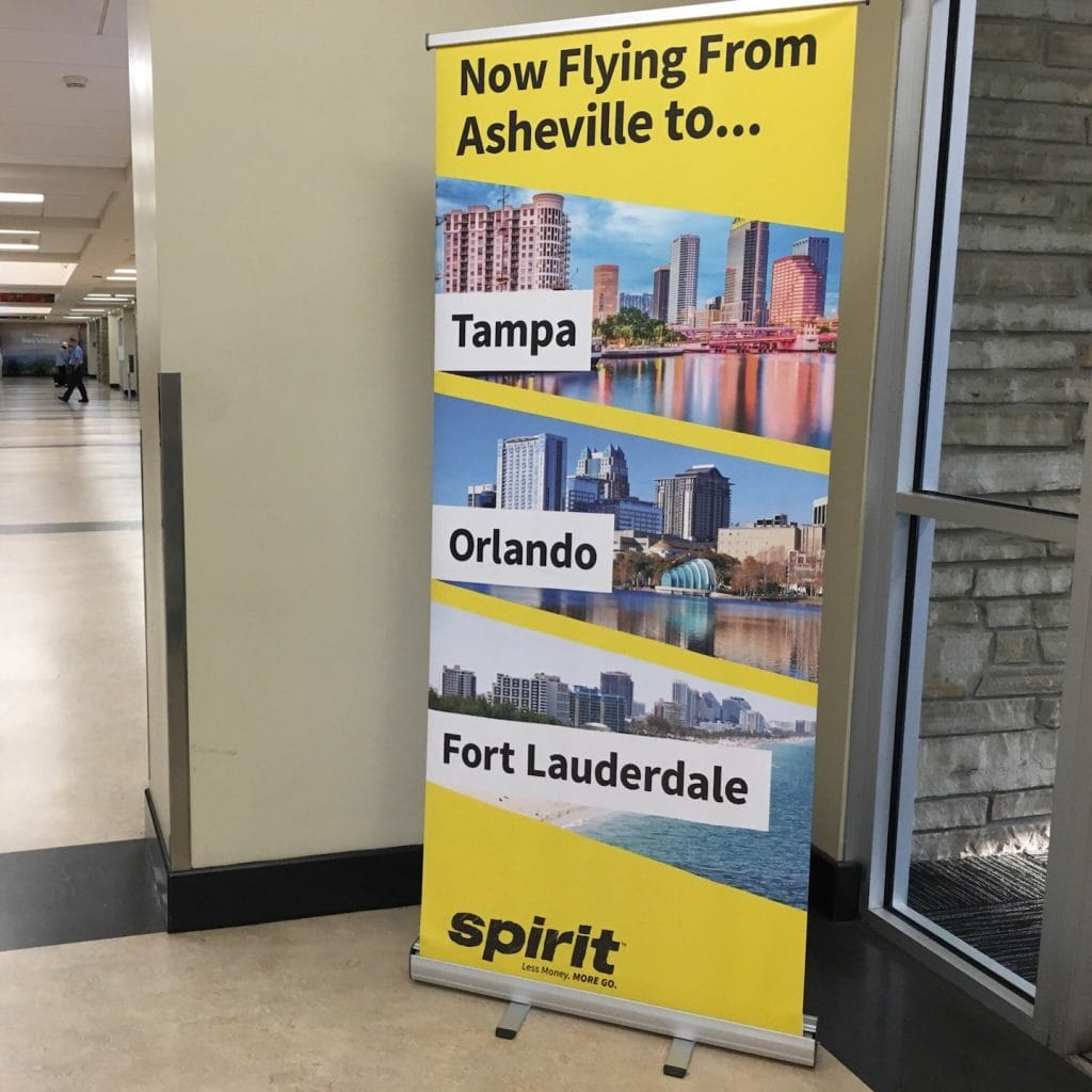 promotional sign for Spirit Airlines from Asheville to Orlando and Florida cities