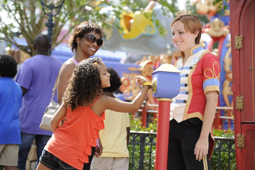 Mother and Daughter at Disney World holding MagicBand to touchpoint at Storybook Circus in Magic Kingdom theme park