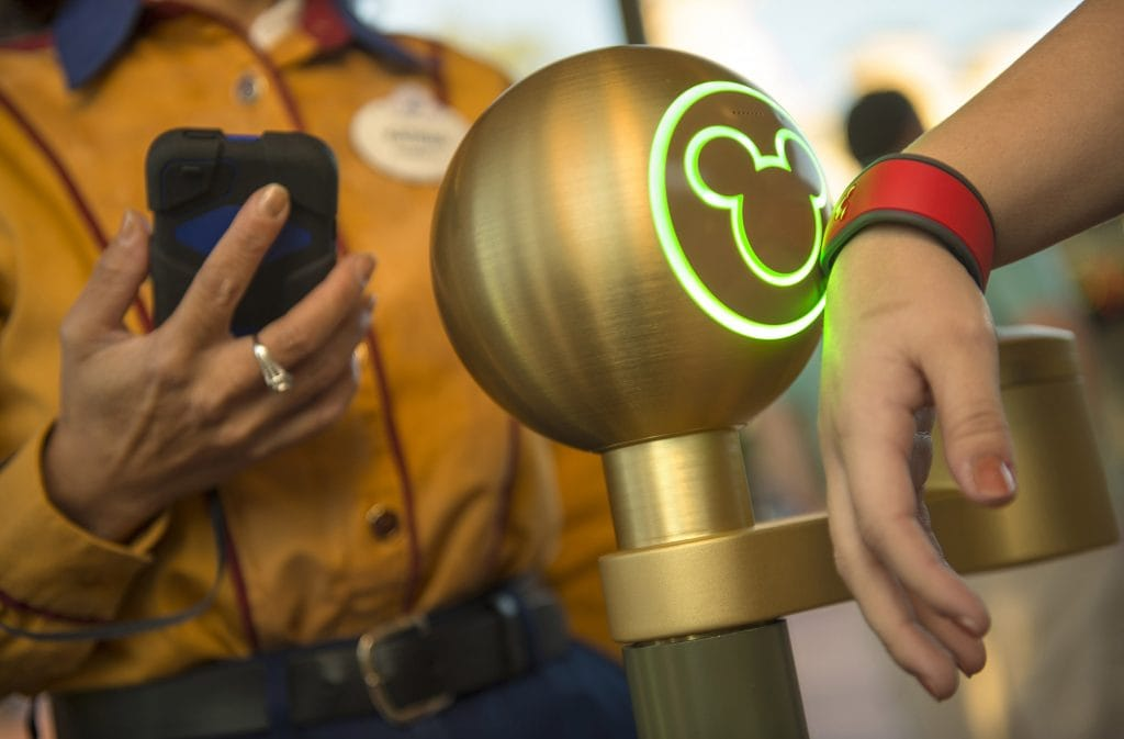 gold metal ball with green neon Mickey Head lit up and person wearing red bracelet at Disney theme park