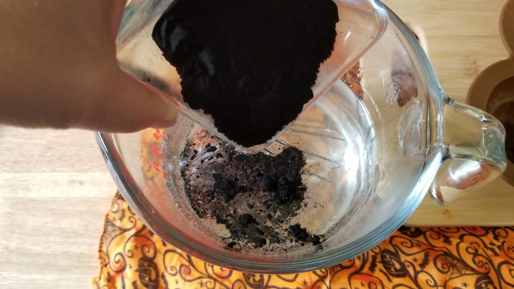 adding black activated charcoal to melted soap in a glass bowl