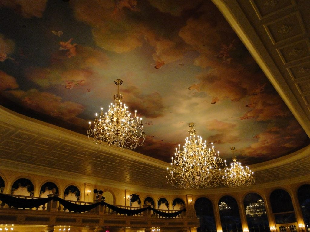 Painted ceiling with clouds and glass chandeliers at Be Our Guest Restaurant