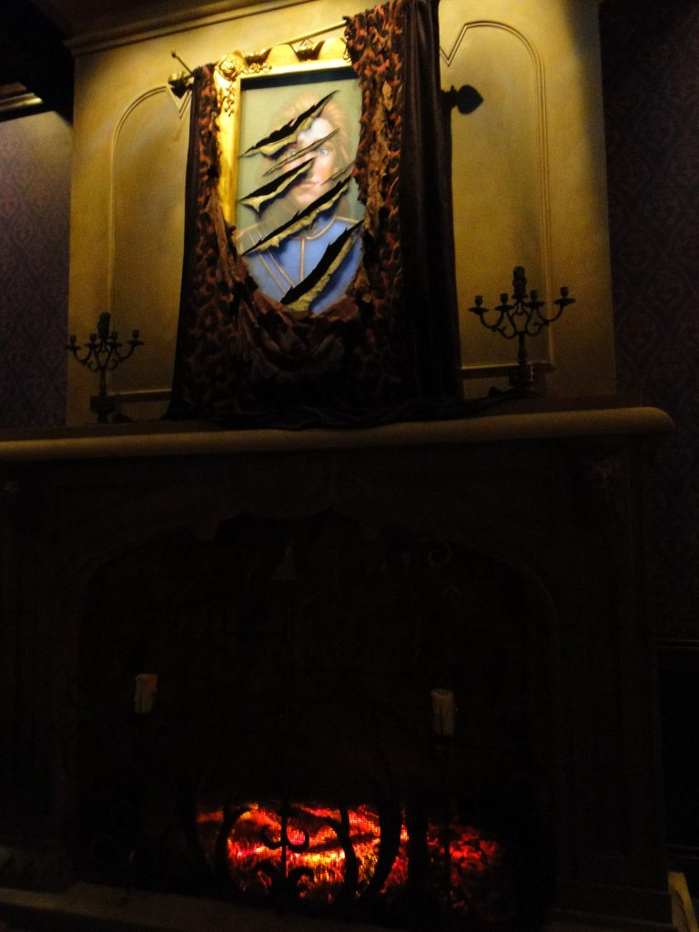 torn painting from Beauty and the Beast on wall above fireplace in Be Our Guest Restaurant